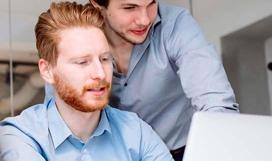 dos hombres miran a un ordenador